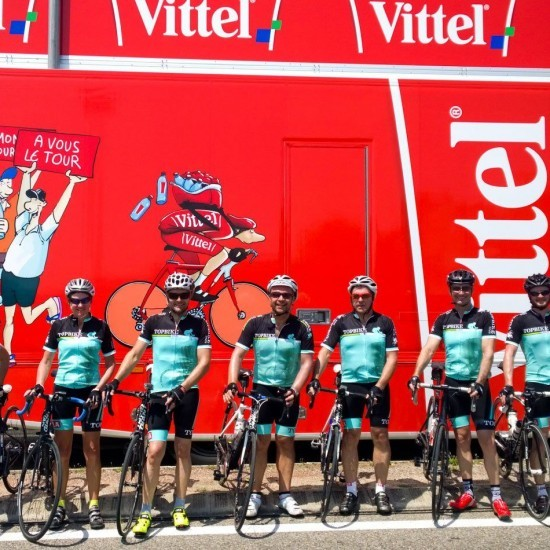 Topbike Riders line up with the TDF Caravan at a stage start during the Tour de France Paris Tour